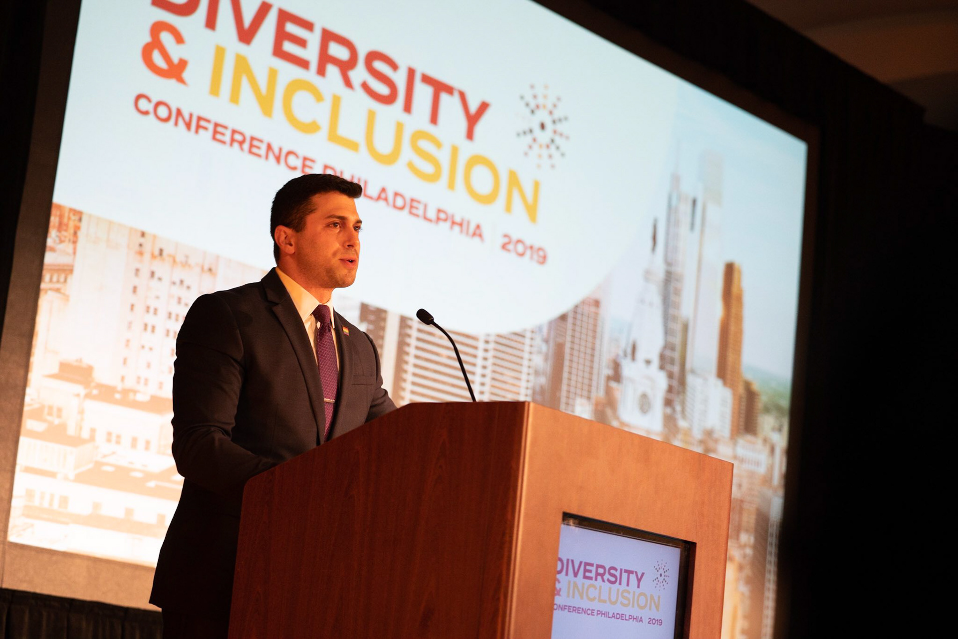 Jonathan Lovitz behind a podium, speaking at the Diversity and Inclusion conference in Philadelphia